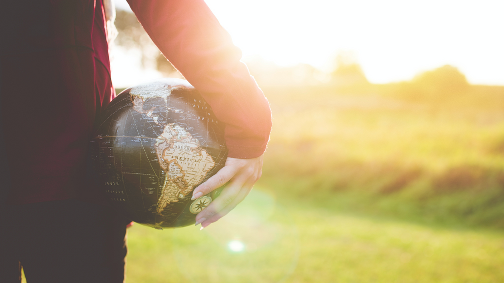 A woman's hand carrying a globe of planet earth.