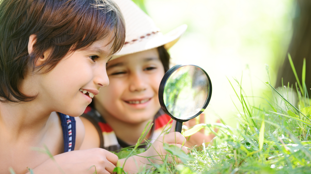 Two kids explore outside with a magnifying glass.