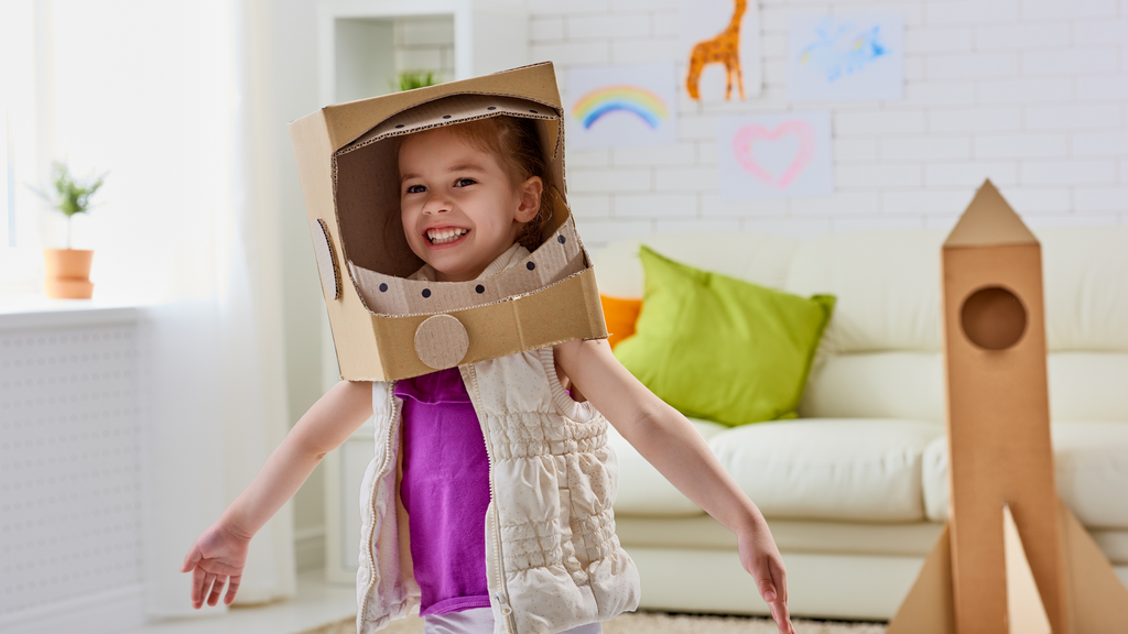 A girl wears her homemade astronaut costume made out of cardboard.