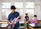 Student in classroom playing music with electronic littleBits guitar.