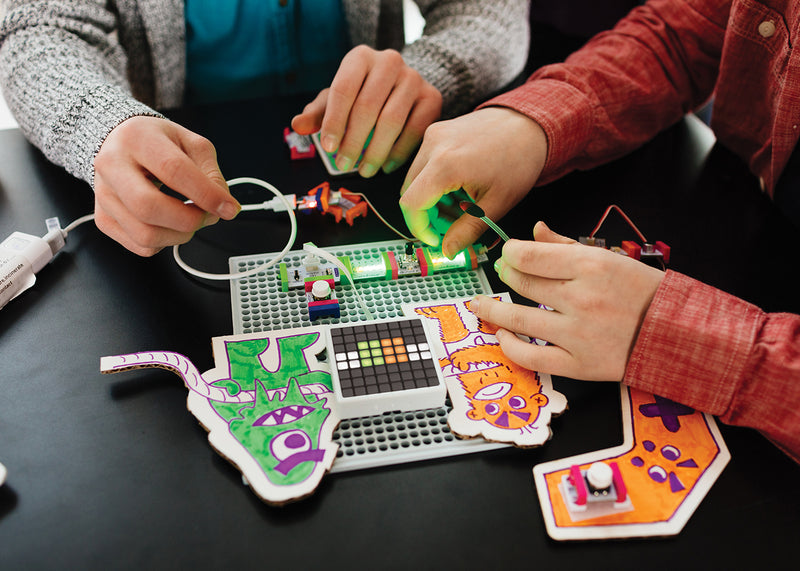 Kids snapping littleBits together to make an arcade game.