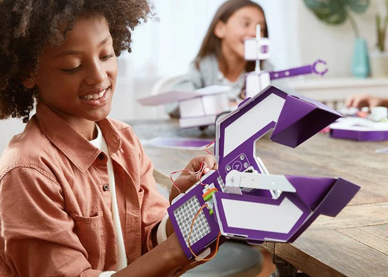 Girl having fun learning STEAM with littleBits invention.