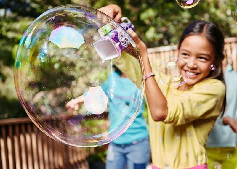 Young girl playing with STEM bubble bot outside.