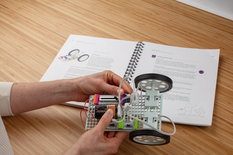 Teacher using guide to build a car invention out of littleBits circuits.