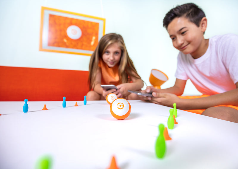 Girl and boy playing with orange mini robots in a lane of pins and cones.