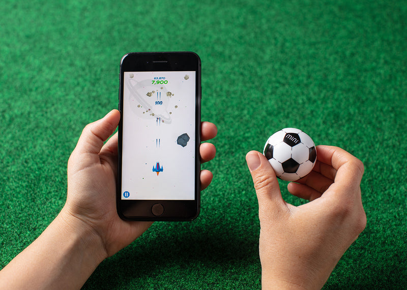 Mini Soccer being used as a game controller next to a smartphone with a space game on the screen.