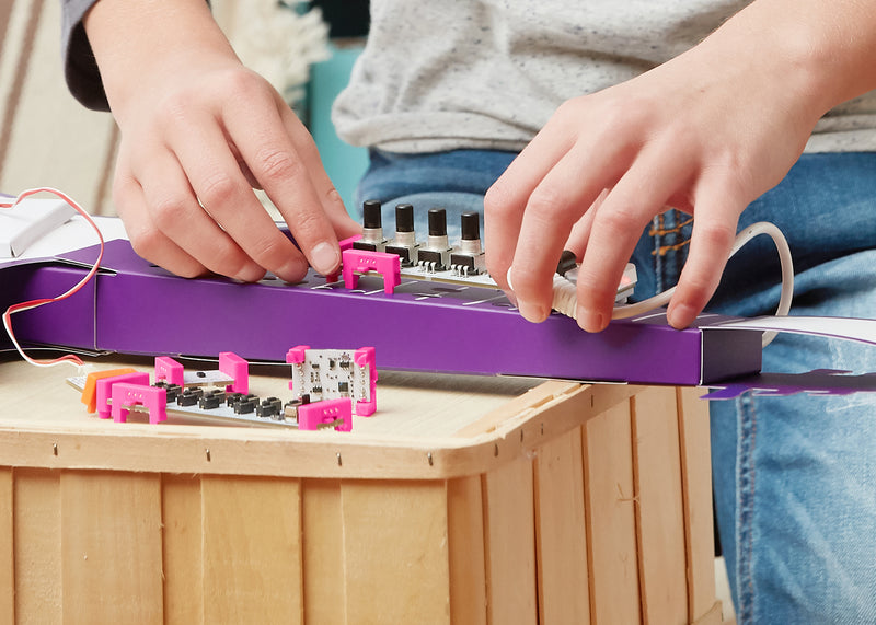 Kid playing with littleBits music invention.