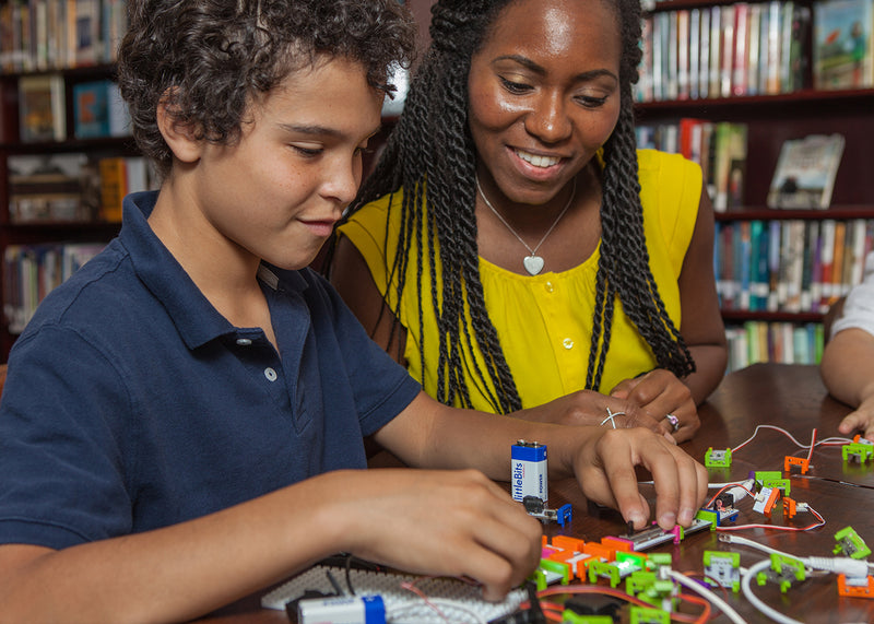 Teacher and student putting together littleBits near a bookshelf.