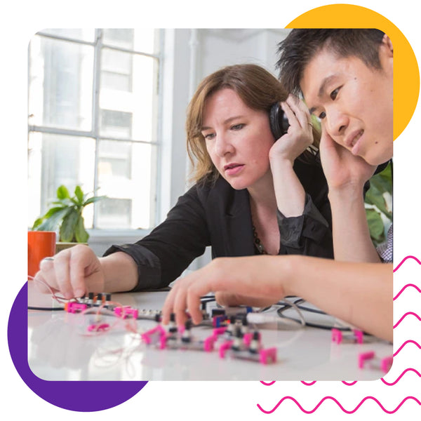 Two teachers working together on a littleBits project while listening to instructions on headphones.