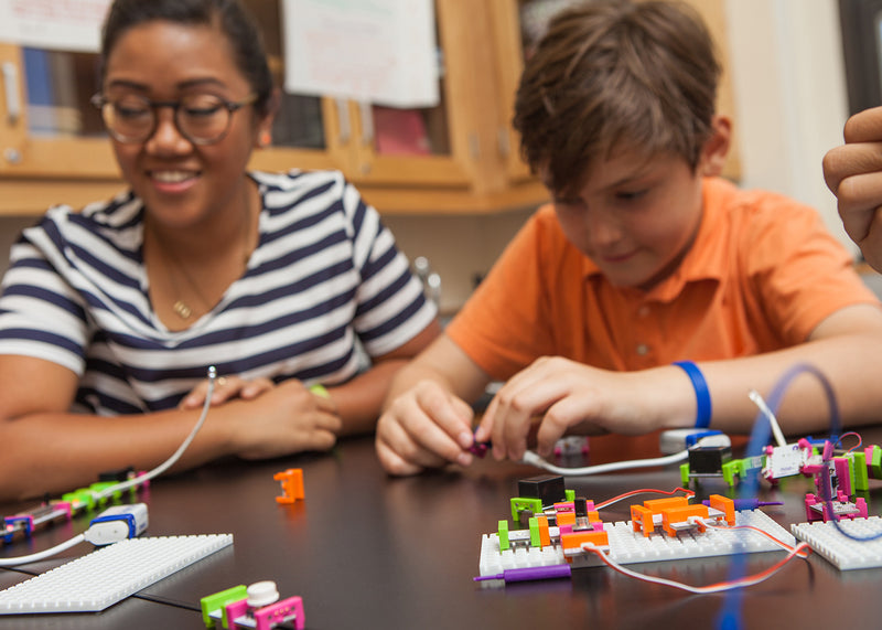 Teacher working with young student on littleBits project.