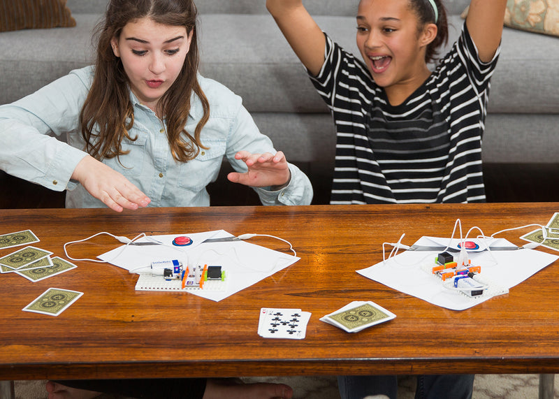 Two girls having fun playing with cards and littleBits inventions.