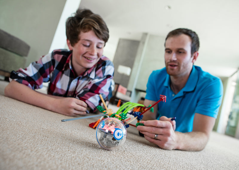 Father and son on living room floor building a chariot with STEM robotic toy.