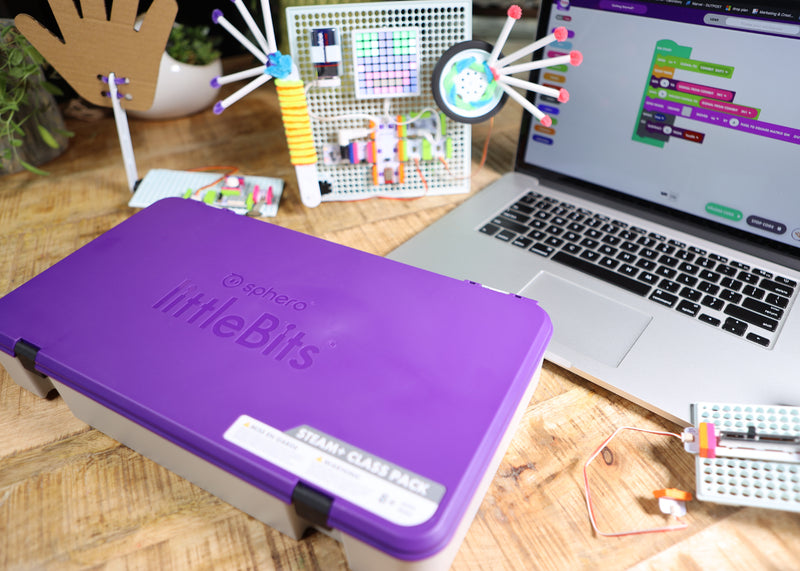 Two littleBits inventions next to tackle box and laptop with code blocks.