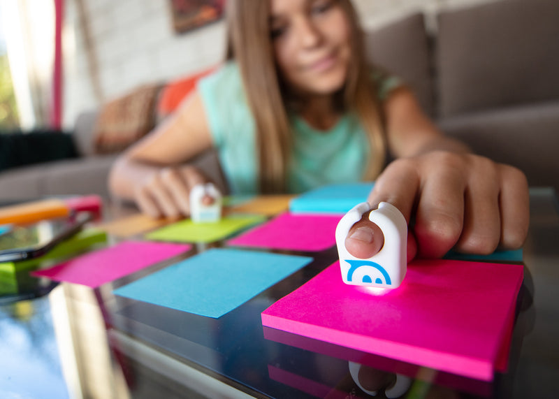 Girl playing with Specdrums rings on post-it notes.