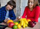 Girl and boy having fun playing Specdrums rings on fruit.
