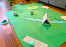 Mini golf course made out of construction paper and household items in a living room.