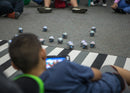 Student playing with multiple BOLT toy robots on tablet.