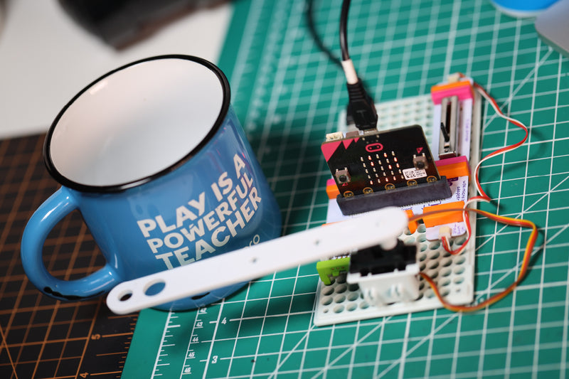 micro:bit clock invention with littleBits arm tapping a coffee mug.