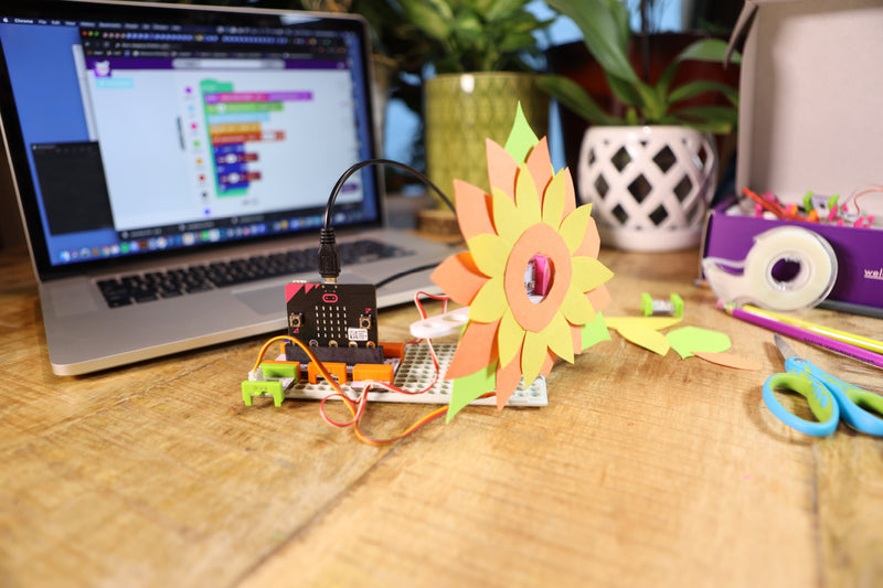 Sunflower micro:bit invention with craft supplies and laptop in the background.