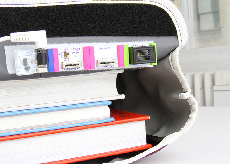 Bit from littleBits STEAM Student Set peeking out from backpack.