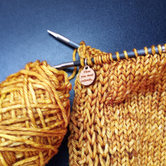 Golden Yarn on a black background with wood stitch marker