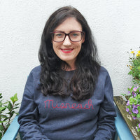 Deirdre Collins founder of Hoopla Focal, seated outdoors in front of a cream wall with plants.. Wearing a navy sweatshirt with Misneach embroidered in chilli colour thread