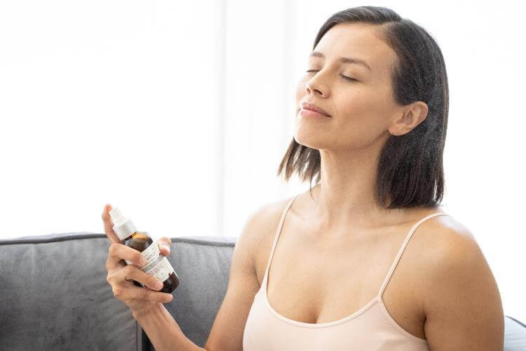 A beautiful woman looks calm and serene while spraying organic rose phyto facial mist onto her face.
