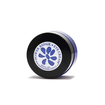 A 0.5 oz. container of Power Repair Eye Cream by Peak Scents and Super Salve Co. in a round blue glass container