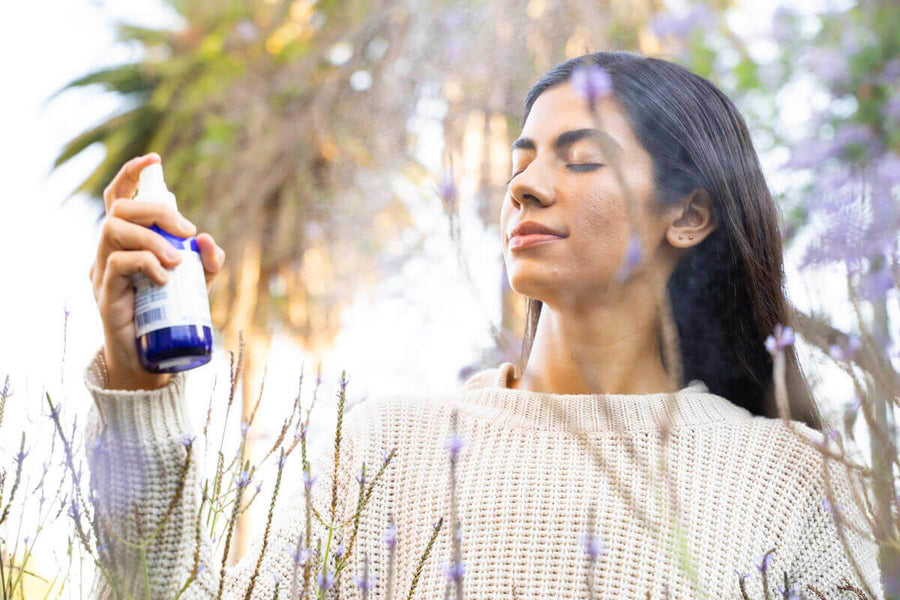 A woman Sprays herself with the Power Repair face mist. She is standing amongst trees and flowers and look quite serene.  Edit alt text