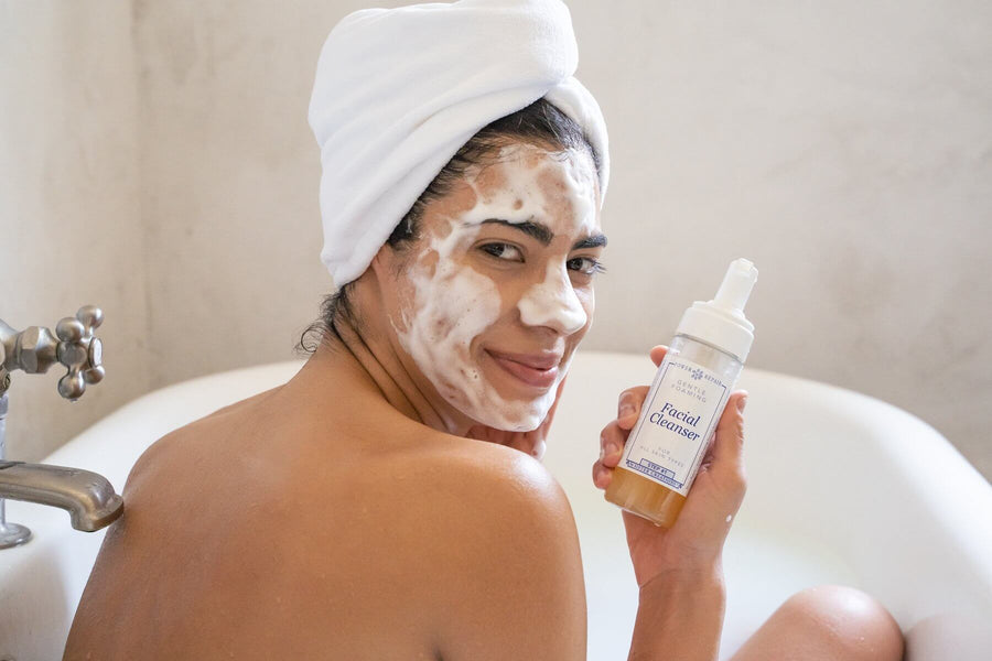 A woman in a bath tub has Power Repair Skin Cleanser by Sister Creations into her face. It is Foamy, she looks happy, and there is a towel on her head.