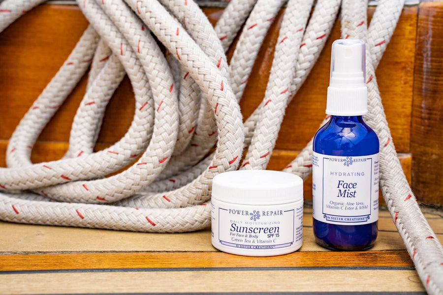 The Power Repair Face Mist and Power Repair sunscreen are sitting on the deck of a boat, ready to be used in an adventure.