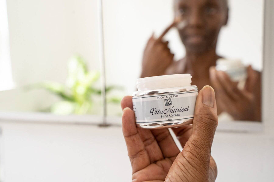A beautiful black woman is applying the Vita Nutrient Face Cream to her face while holding the container in her hand.