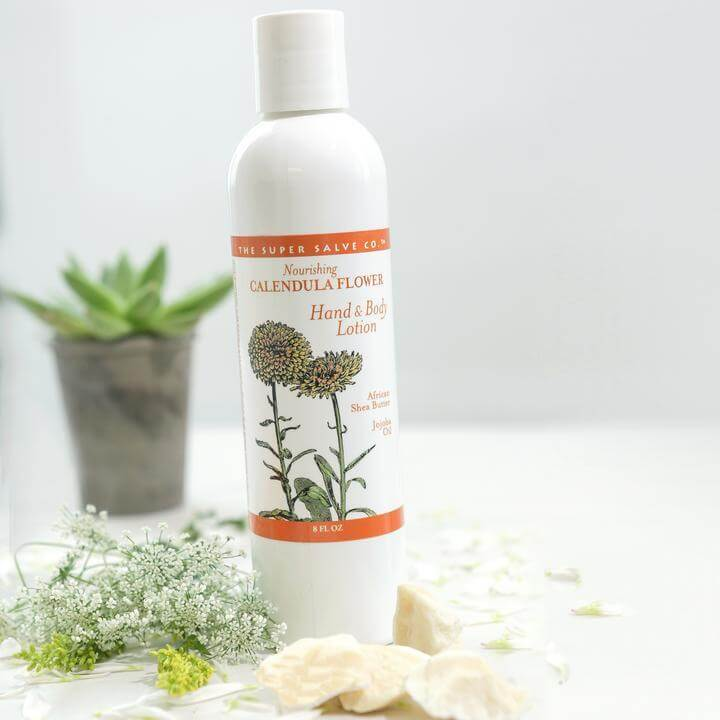 Calendula Flower Lotion 16 oz. set next to some beautiful plants with a pristine white background.