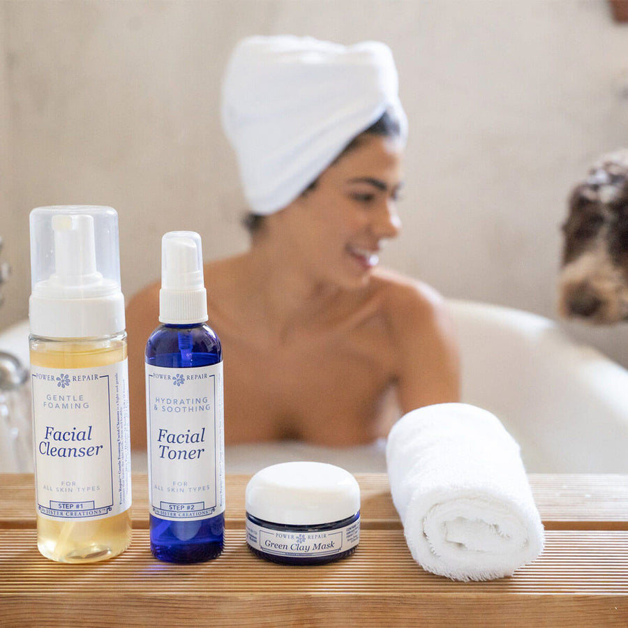 A woman is smiling in the bathtub while her cute dog with curly hair peers in. The Power Repair Skin Care line is sitting in front of her on a shelf.