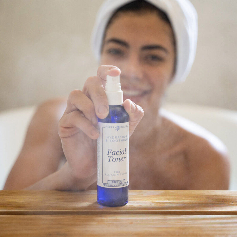 A woman joyfully spraying the Power Repair Facial Toner, while she is smiling in the bath tub.