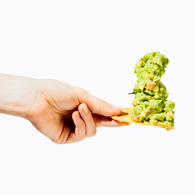 A hand holding a chip with a large amount of  guacamole on it.