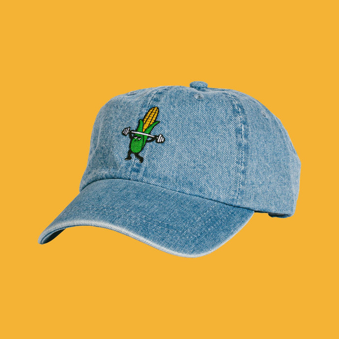 Denim hat with a corn cob lifting weights. Front view.