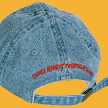 "Load image into Gallery viewer, Denim hat with red lettering ""Zack's Mighty Tortilla Chips"" on the back."