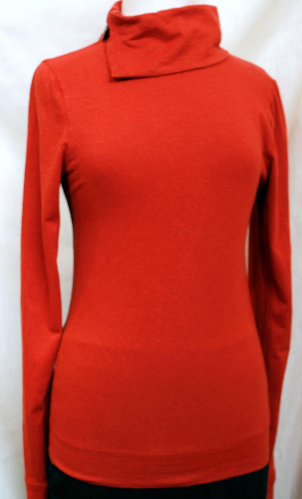 hemp long sleeve top with one button holding together the turtle neck neckline in a tangerine red/orange colour