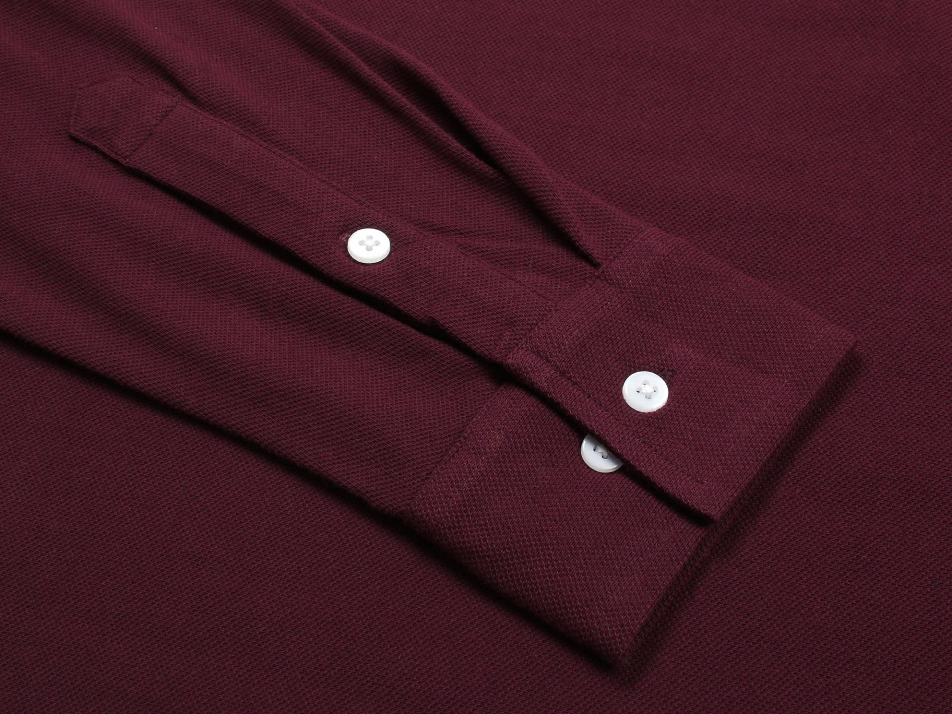 Detail of white buttons on wrist sleeve of burgundy shirt. Adjustable sleeve length to roll up