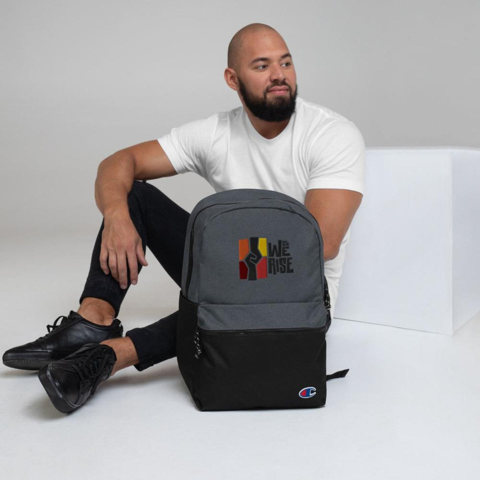 African American man posing with black-grey embroidered And Still We Rise logo backpack