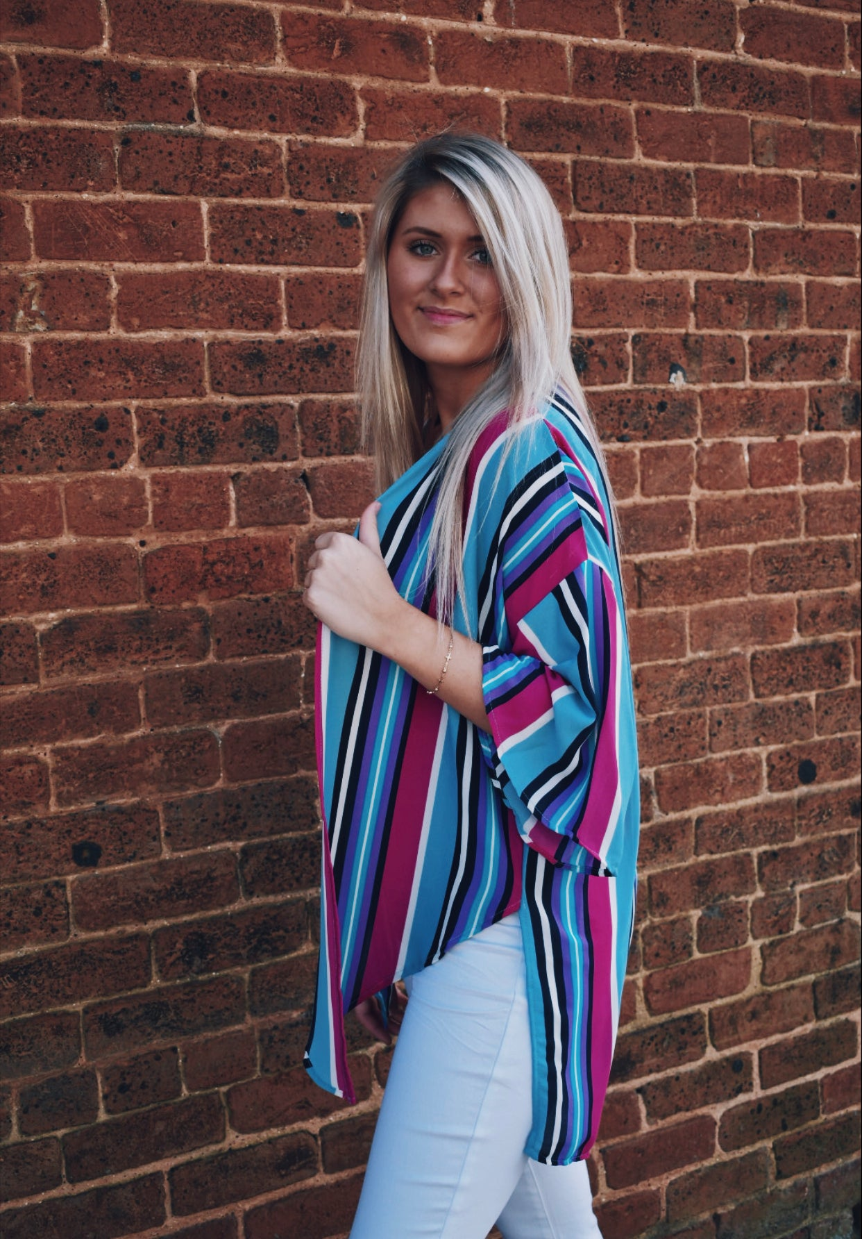 Brand new to our boutique! Lighten up your wardrobe with this Multi-Colored Striped Kimono! The breezy, lightweight material makes it perfect for layering over almost anything! Also fits true to size.