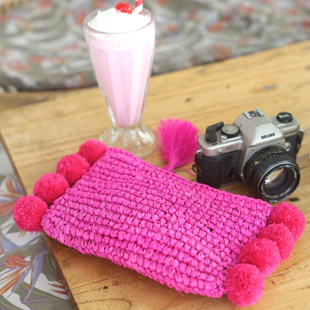 Brunna Canggu Woven Straw Clutch in Hot Pink Raffia & Pom-poms