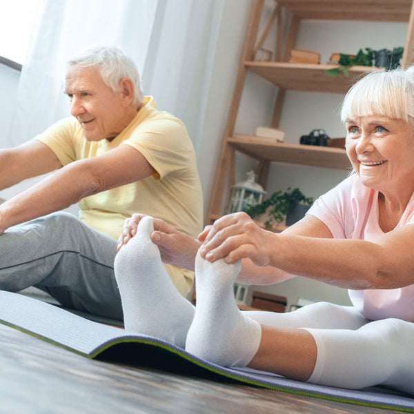 Older man and woman doing yoga exercise at home