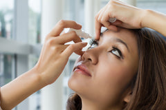 woman putting eye drops in her eyes