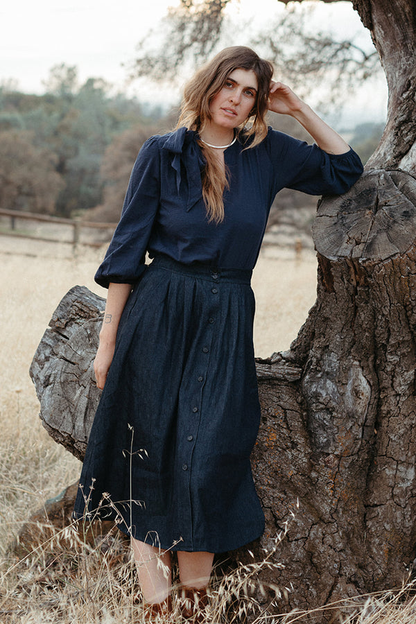 Dark denim button up maxi skirt on standing model, paired with dark blue button up blouse