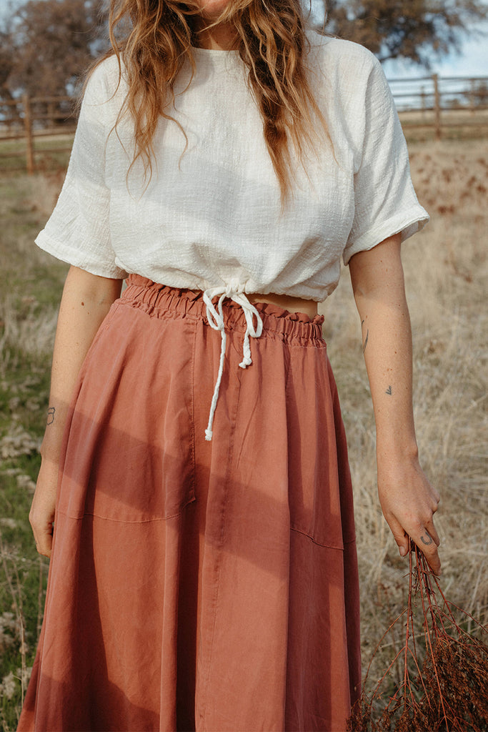 Pink elastic waist skirt on standing model, paired with white short sleeve top