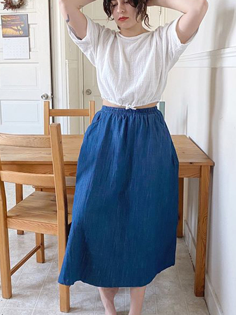 Blue denim maxi skirt on standing model, paired with white short sleeve top