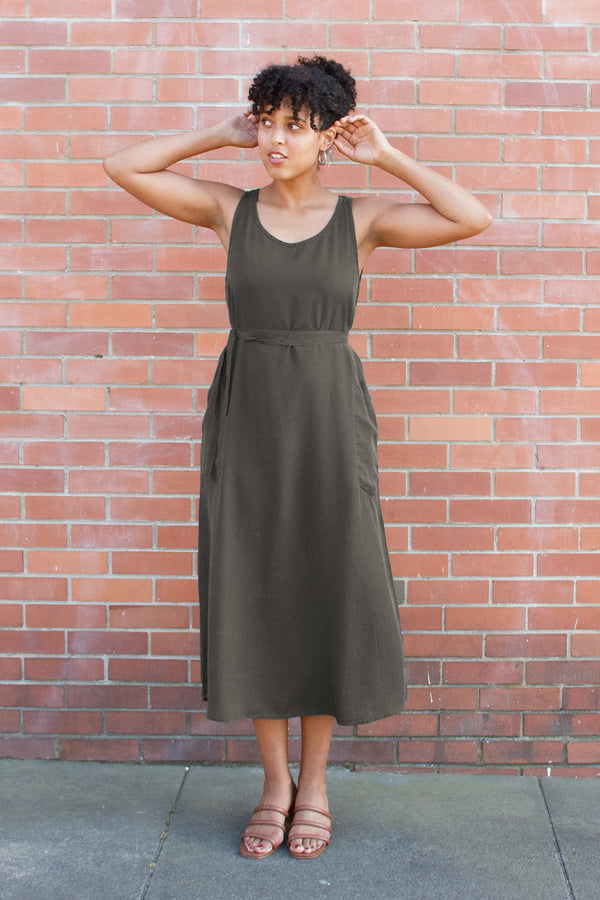 model in army green sleeveless dress with cinched waist