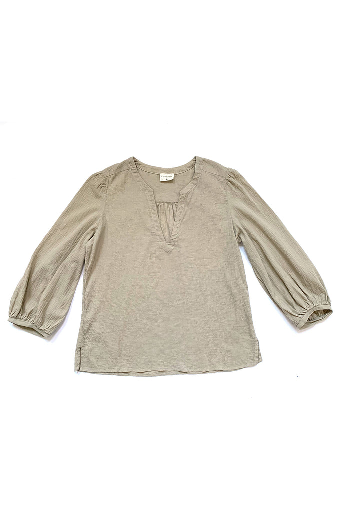 beige blouse with long sleeve flat on white background